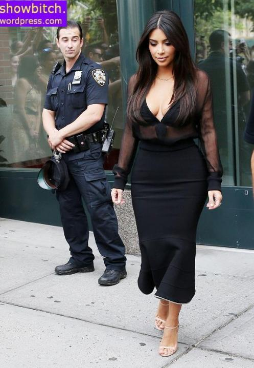 COP A VIEW! Kim Kardashian leaves her apartment with an NYPD officer appearing to stare at her backside